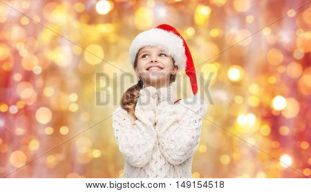 christmas, holidays and children concept - dreaming girl in santa helper hat over lights background