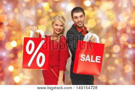 christmas, holidays, discount and people concept - couple with sale and percentage sign on red shopping bags over lights background