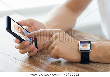 business, technology, communication and people concept - close up of male hands on wooden table holding smartphone and wearing smart watch with incoming call on screen