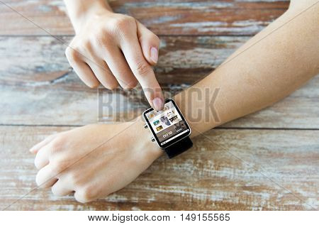 business, modern technology, blogging, media and people concept - close up of female hands setting smart watch with internet blog on screen on wooden table