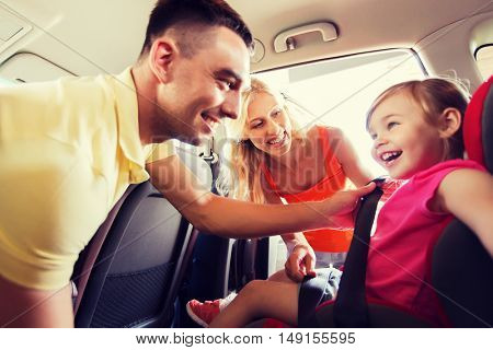 family, transport, road trip and people concept - happy parents fastening child with safety belt in baby car seat