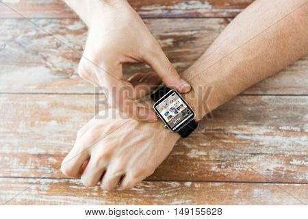 business, modern technology, blogging, media and people concept - close up of male hands setting smart watch with internet blog on screen on wooden table