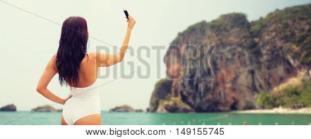 summer, travel, technology and people concept - sexy young woman taking selfie with smartphone over bali beach and rock background