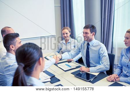 business, people, partnership, gesture and startup concept - group of smiling business people meeting and shaking hands in office