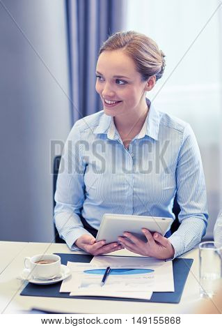 business, people and technology concept - smiling woman with tablet pc computer, papers and cup of coffee in office