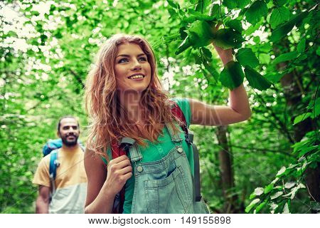 adventure, travel, tourism, hike and people concept - happy couple walking with backpacks in woods