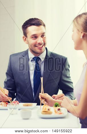 restaurant, couple and holiday concept - smiling couple eating sushi at restaurant