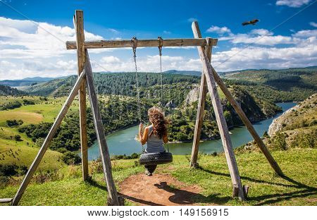 Beautiful woman on the swing with panoramic view on Meanders at rocky river Uvac, southwest Serbia.