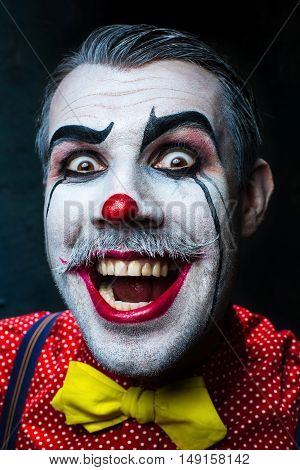 Terrible clown and Halloween theme: Crazy red clown in a shirt with suspenders on a dark background
