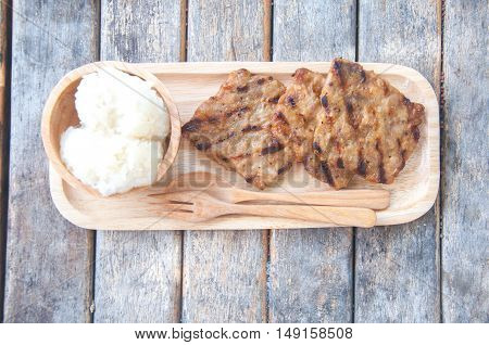 Thai street food style grilled pork with sticky rice on wood table