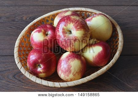 Red apples autumn harvest in a small wicker basket on wooden boards