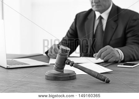 Hands of lawyer and gavel on wooden table. Retro style