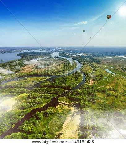 Summer landscape in rich colors from above with balloons in the background. Aerial view. Outdoor. Lush green field with river and backwater skyline.