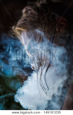 The profile of smoking hipster man with long hair