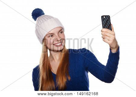 Attractive young girl smiling and making selfie on the phone. Dressed in winter hat and sweater. White background.