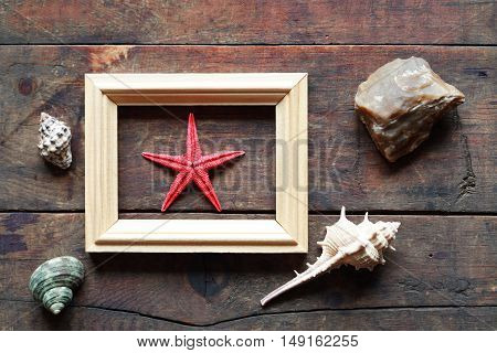One red starfish inside frame on old wooden background