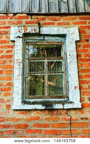 Old window in the vertical colored composition with a old dirty wall of bricks