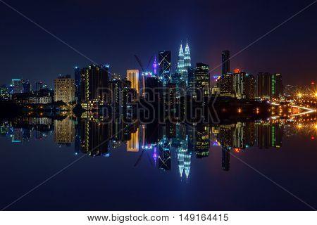 Majestic View Of Kuala Lumpur City Skyline At Night With Full Reflection.