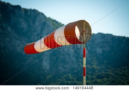Horizontally flying windsock (wind vane) due to high wind. Blue sky and high mountains in the background.