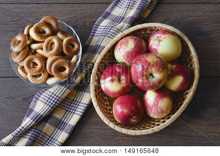 Basket with red apples, vase with dry bread-rings and towel
