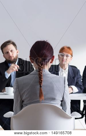 Young woman sitting in front of recruiters during job interview