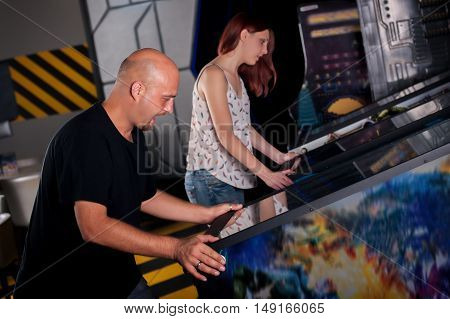 People playing pinball at arcade in game room