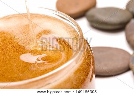 Wave flowing of natural sweet honey in glass bowl
