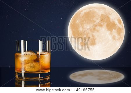 Whiskey glass on midnight sky with full moon background. Cognac glass. Brandy glassful. Cognac france. Full moon and scotch drink. Full moon on the night sky. Full mystic Moon.