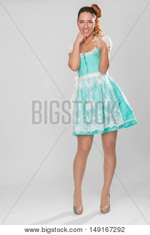 Positive young woman high in Dirndl with thumbs.