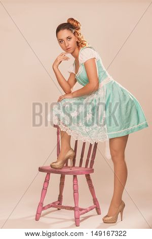 Young woman standing with one leg on a chair and is lost in thought.