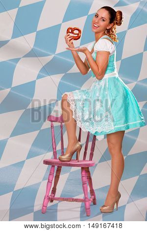 Young girl in Bavarian dirndl presents a pretzel of white / blue diamonds background