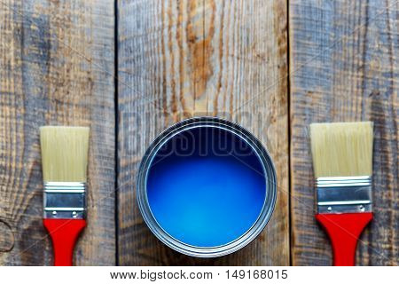 painting at home with open can of blue paint and red brushes on wooden background top view