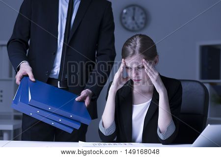 Shot of a stressed young worker sitting at her desk