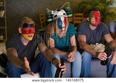 Shot of international friends with their faces painted watching a football game together