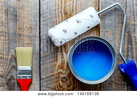 painting at home with open can of blue paint and red brush on wooden background top view