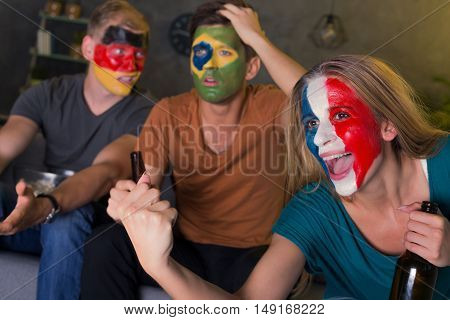Shot of a happy French football fan and her disappointed friends