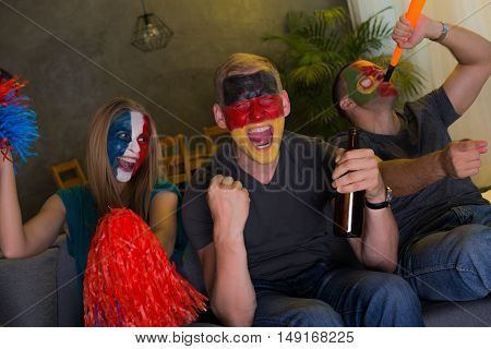 Shot of happy football fans supporting their teams with flags painted on their faces