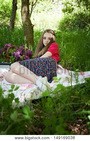 Beautiful Teenage Girl Sitting On A Blanket In A Forest