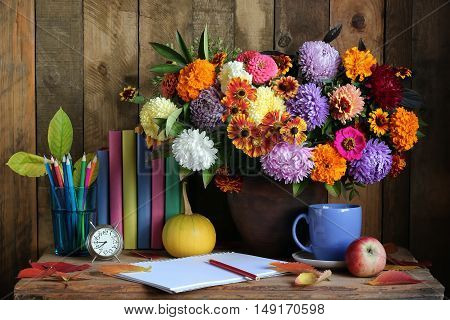 Still life with a bouquet of fall flowers books and colored pencils. Back to school.