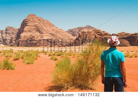 Photo of the Stylish man wearing trendy hat and T-shirt looking at amazing landscape enjoying life. Traveler freedom travel luxury vacation active life concept.