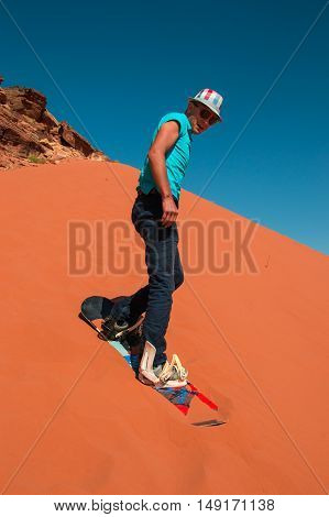 Photo of the Stylish man sand boarding in desert down red dune Wadi Rum Jordan. Active rest travel healthy lifestyle concept.