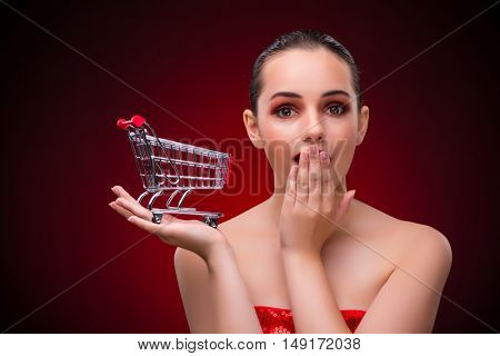 Woman with shopping cart against red background