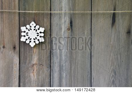 Wooden handmade snowflake on the old wooden background. Christmas. Holiday Winter. Traditions. Season. Holiday decorations to create an atmosphere.