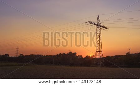 power line in the nature - electricity by sunset