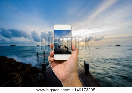 Mobile smart phone behind a of sea beautiful
