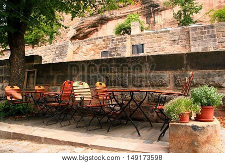 Germany. Nuremberg. Street cafe on the background of the ancient wall