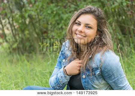 Portrait of laughing head tilted back teenage girl sitting outdoors. Girl is looking at the camera.