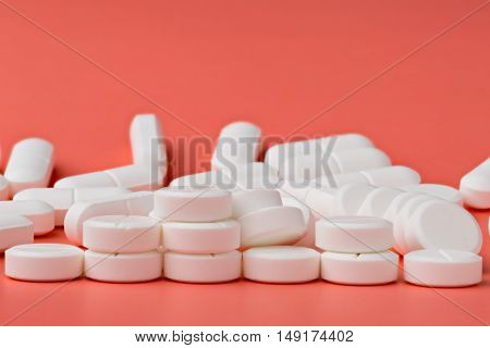 Heap of white round pills on pink background
