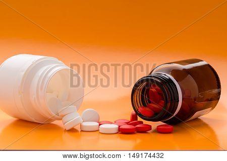 Various pills bottles and heap of pills
