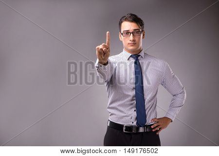 Young handsome businessman pressing buttons on gray background